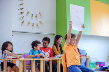 Head of the class in preschool present paper poster reading as Back to school in classroom with group of friends and teacher kindergartner stay in row background