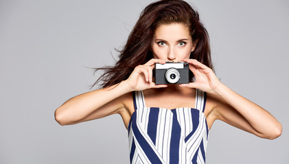 Beautiful and cheerful women model poses with old camera