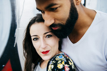 Cheerful couple embracing at street