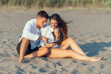 Young couple in love using smart phone on the beach