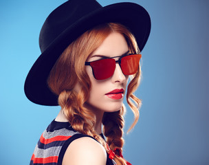 Fashion Model Sexy Girl. Hipster woman Cheeky emotion. Stylish Summer Outfit. Redhead woman in Fashion Sunglasses, Glamour Hat. Trendy Black fashion Hat. Playful Summer Hairstyle