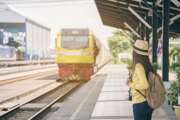 Female Backpack looking at and waiting train in the railway,tourism traveler standing at train station.Travel and Backpacker Concept.