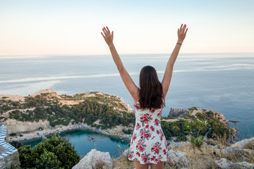 View from top on Anthony Quinn Bay and beach, Rhodes in Faliraki, Greece. Happy girl Raising One Hand. Beautiful beach and bay on the island of Rhodes.