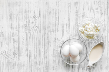Farm dairy products. Milk, cottage, eggs on light wooden background top view copyspace