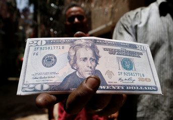 An Egyptian man carries a wallet with the picture of a dollar bill during the holy month of Ramadan in old Cairo
