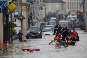 French firefighters use a small boat to evacuate residents from a flooded area after heavy rainfall in Nemours