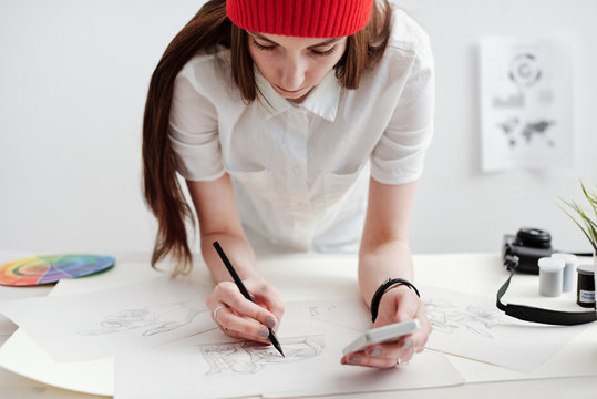 Young female designer creating sketches and infographics