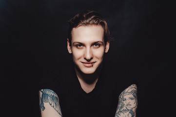 Portrait of a young blond guy with tattoos and piercings on a black background