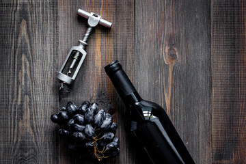 Open wine. Bottle and corkscrew on dark wooden table background top view copyspace
