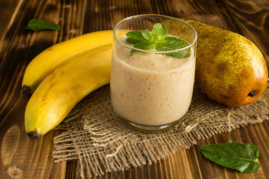 Smoothie from banana and pear on the brown wooden background