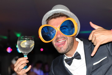 Fun looking man at a party holding a cocktail and sticking his tongue out