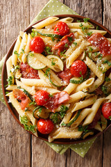 Delicious hot penne pasta with ham, cherry tomatoes, zucchini and cheese close-up. Vertical top view