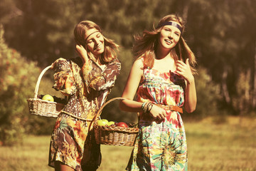 Happy young fashion girls with a fruit basket walking outdoor