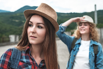 Two girls in hats traveling and hitchhiking