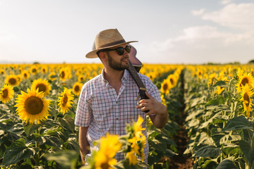 Carefree man with a guitar on his back in a sunflower field