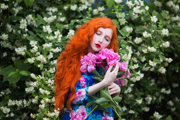 Woman with pale skin and long red hair in peony dress on background of a flower garden. Beautiful girl with red lips with a bouquet of peonies in hands. Beauty makeup. Redhead model. Sensual portrait