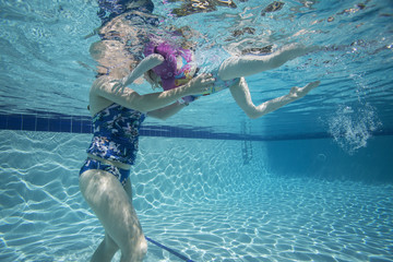 An underwater view of a mother teaching a young girl how to swim.
