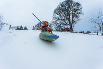 Man sliding down snowy hill in kayak