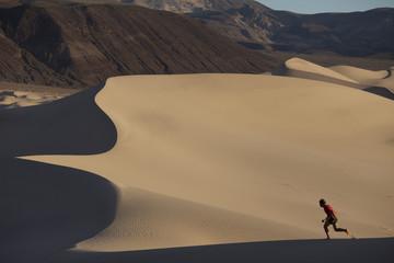 A man running on sand dunes in the desert.