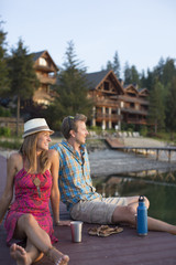 Couple hanging out during summertime on a dock in front of a lodge on a lake.