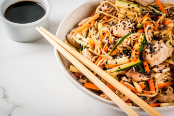 Traditional Asian food. Lunch stirfry: rice noodles, zucchini, carrots, bamboo, mushrooms, pork (beef), soy sauce and black sesame. With soy sauce, chopsticks. Copy space