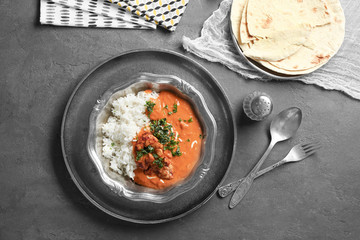 Plate with delicious Murgh Makhani and rice on table