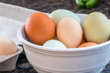 Horizontal photo of multicolored eggs in a white bowl and some in the carton to the side on a kitchen counter with a green pepper in the background