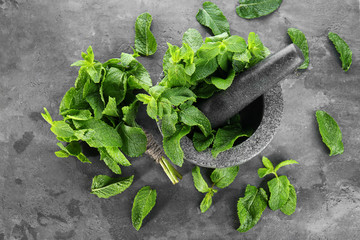 Fresh mint in mortar with pestle on grey background