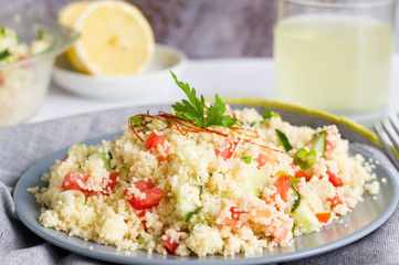 Couscous salad with fresh vegetables served on grey plate on kitchen table.