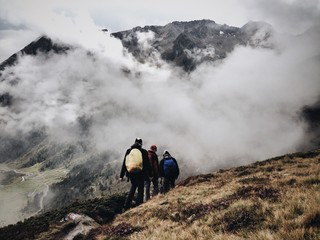 High Angle View Of People Hiking On Mountains Against Clouds