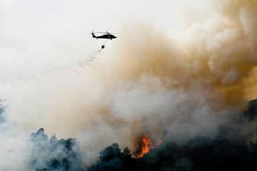 Silhouette Helicopter Extinguishing Forest Fire While Flying Over Mountain
