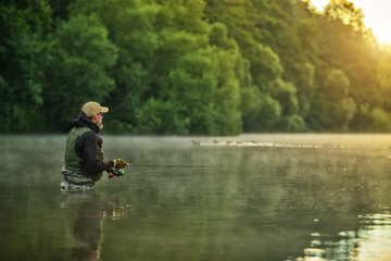 Spoed Fotobehang Vissen Sport fisherman hunting fish. Outdoor fishing in river