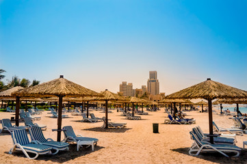 Dubai. Heavenly oasis in Ras al Khaimah. The beach with sunbeds and sunshades in Dubai, on the shores of the Arabian Gulf. Toning.