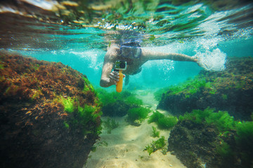 Young man, swimming underwater and making photos