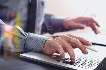 close up of businessman working with mobile phone and stylus pen and laptop computer  on wooden desk in modern office with virtual icon diagram