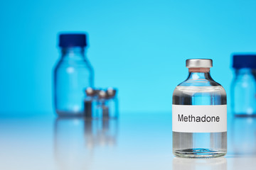 A ampoule of methadone stands on white surface against a blue background on the right. Further laboratory bottles can be seen in the background. (English inscription) in cross-format