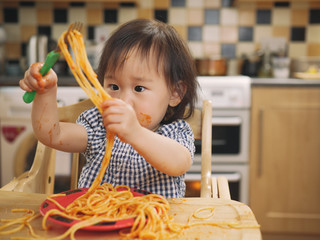 baby girl eating messy spaghetti