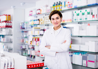 Smiling female pharmacist demonstrating assortment of pharmacy