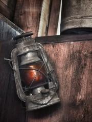 Alte Petroleumlampe an einer Holzwand aufgehängt