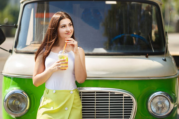 Young pretty woman standing near vintage van with glass of lemonade. Summer heat, refreshment concept