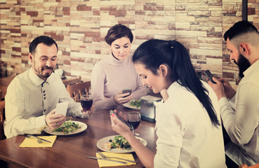 group of young friends busy with phone in restaurant