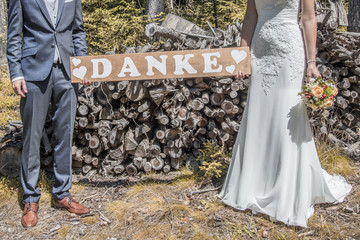 groom and bride with a sign thank you
