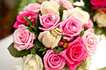 Wedding bouquet white and pink roses with golden rings.