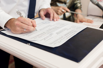 Man leaving signatures registration of marriage close-up