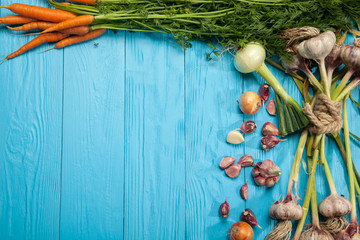 Fresh carrots, garlic and onions on a blue background