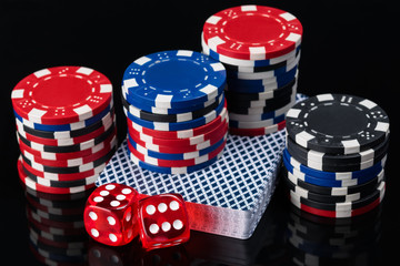 deck of cards and poker chips with cubes on a dark reflective background