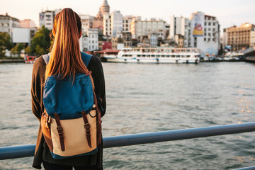 Young beautiful tourist girl with a backpack at sunset next to the Bosphorus on the background of Istanbul. Turkey. Rest, vacation, hiking.