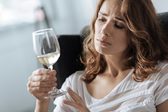 Unhappy beautiful woman looking at the glass of wine
