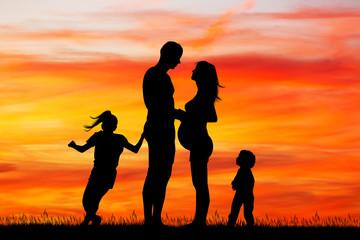 joyful family at sunset