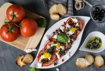 Fresh refreshing salad of mozzarella and red tomatoes on white plate. Spilled with olive oil with pieces of black olives, basil and red onions